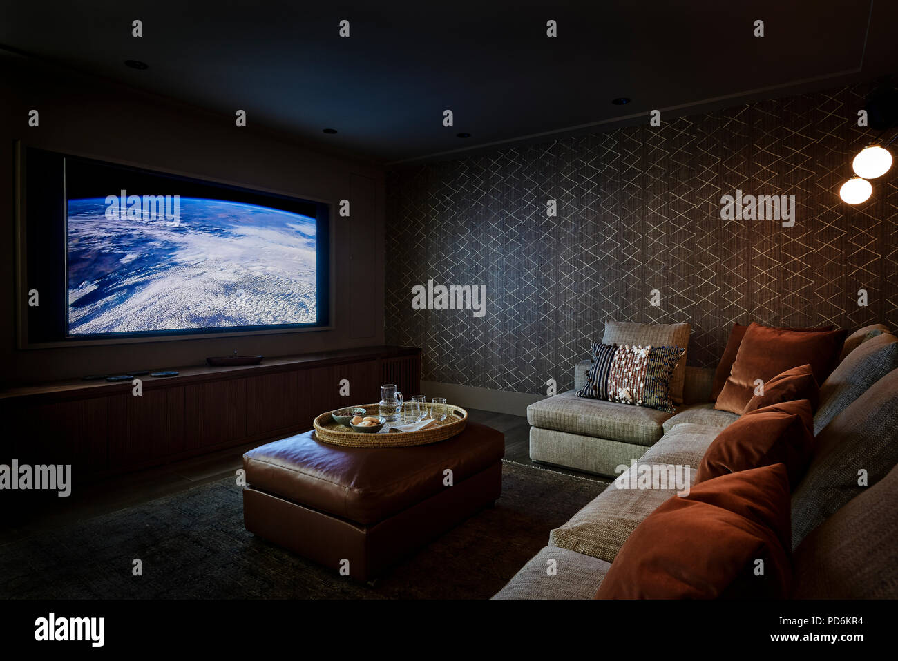 Large screen in home cinema with velvet cushions on corner seating - Stock Image