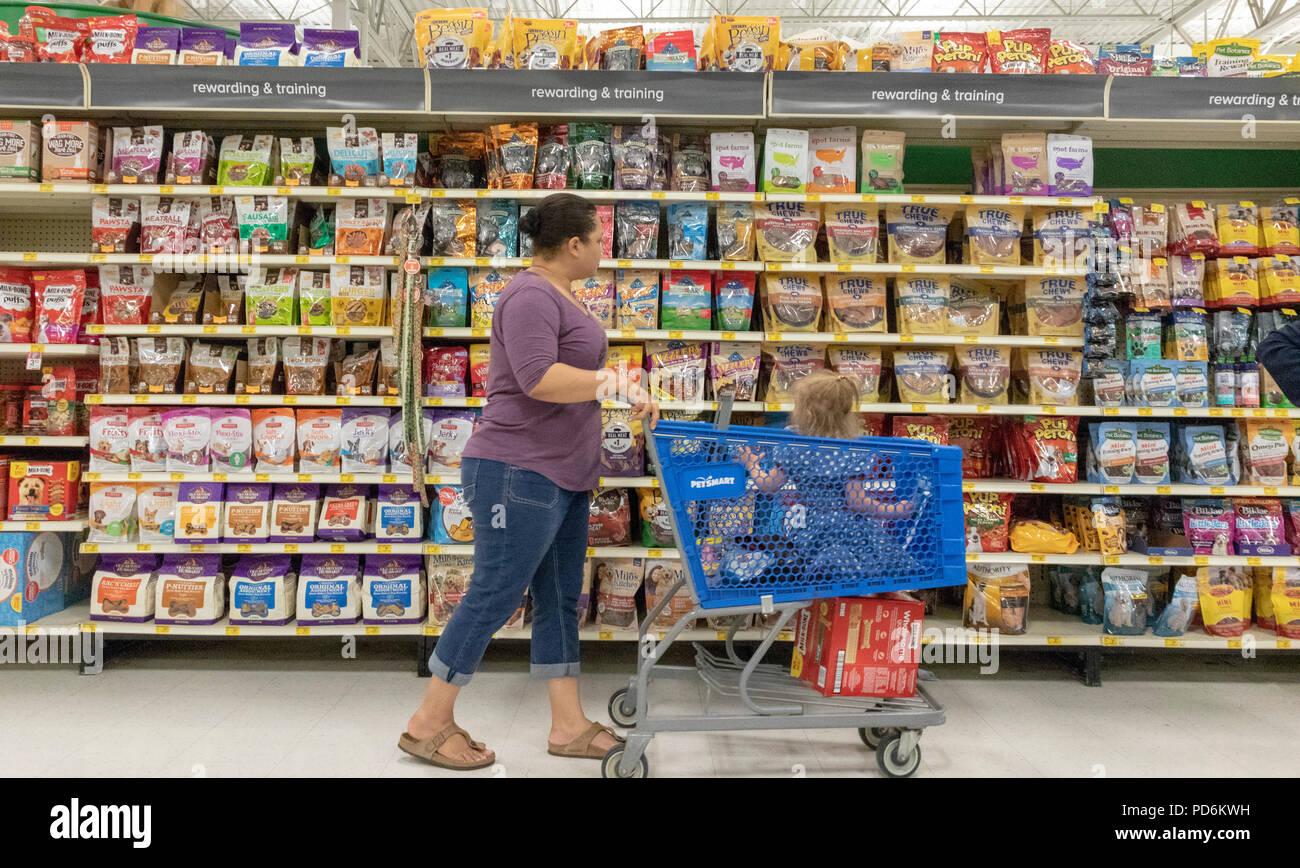 woman with shopping trolley in front of dog reward supplies, PetSmart pet store, Kennewick, Washington, USA - Stock Image