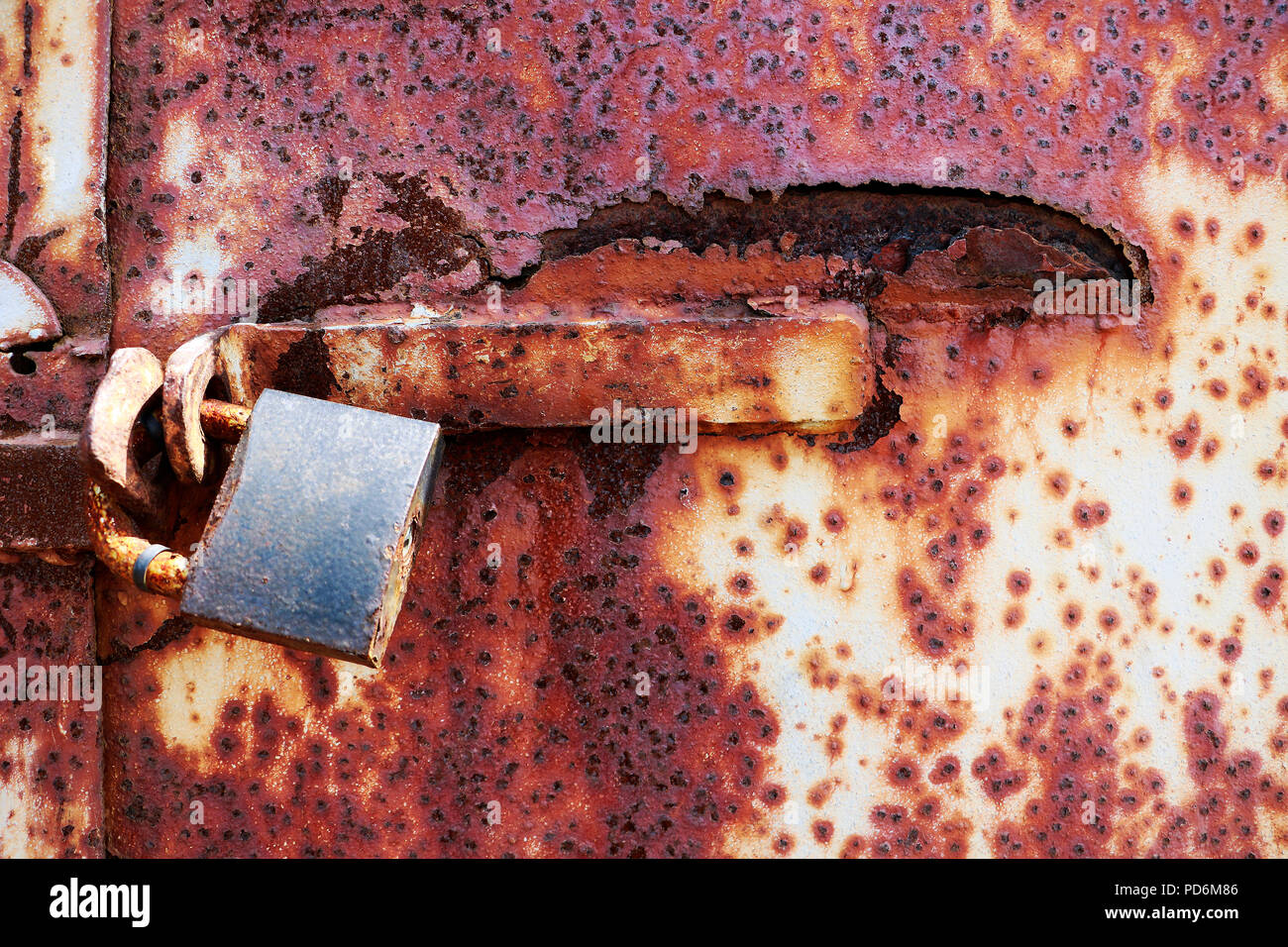 Rusty old lock on red grungy background, textplace Stock Photo