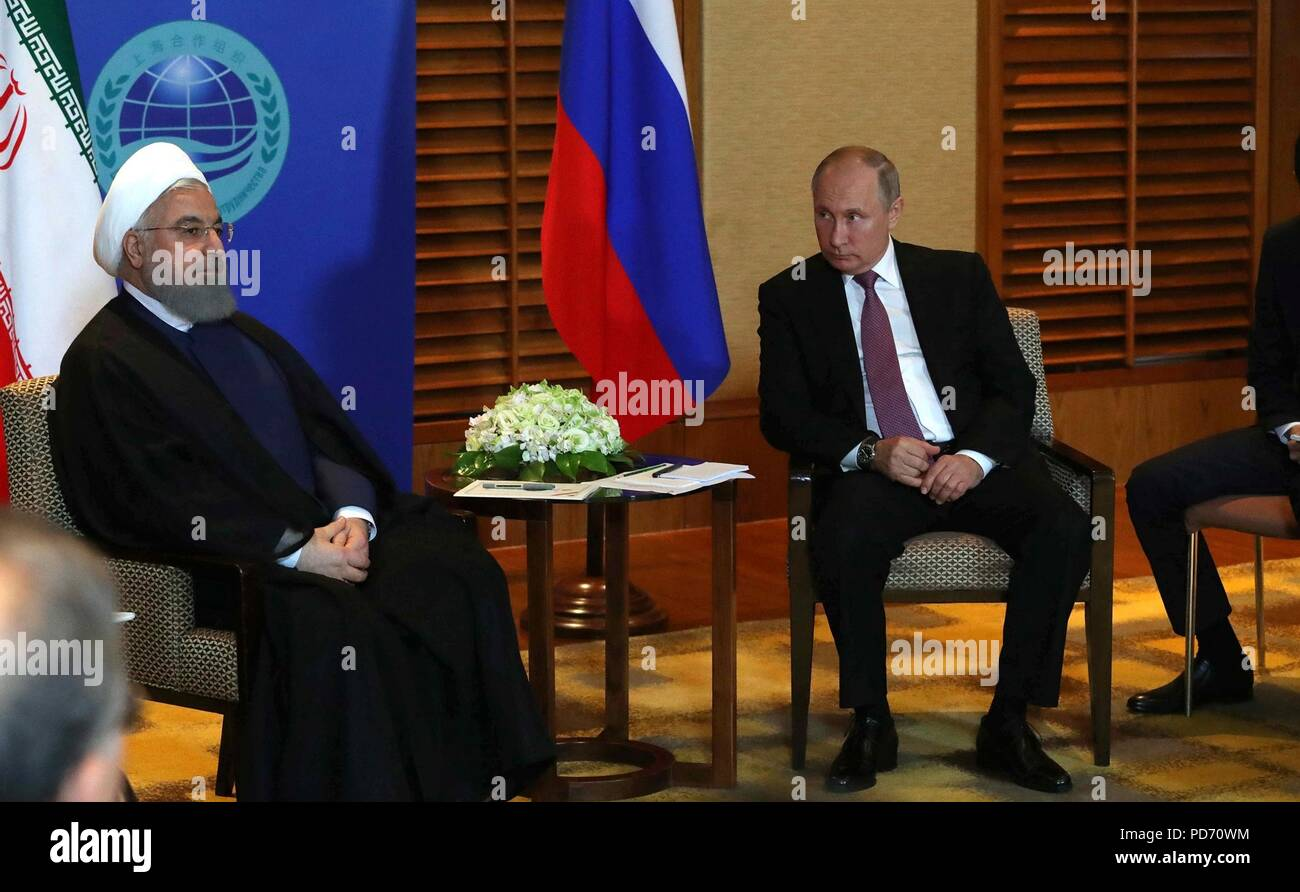 Russian President Vladimir Putin, right, holds a bilateral meeting with Iranian President Hassan Rouhani on the sidelines of the Shanghai Cooperation Organisation Summit June 9, 2018 in Qingdao, China. - Stock Image