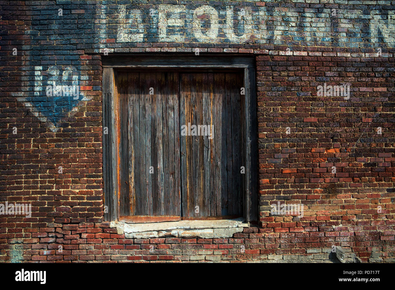 A weathered wooden door and old, fading advertisement painted on the side of a red brick wall in Nashville, Tennessee - Stock Image
