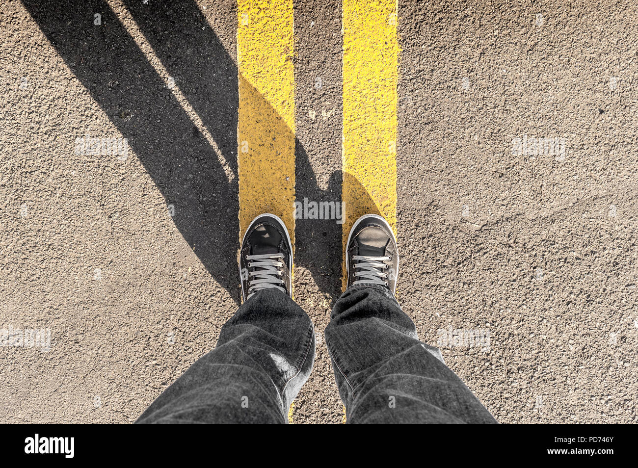 Personal perspective of person's legs and street's yellow lines - Stock Image