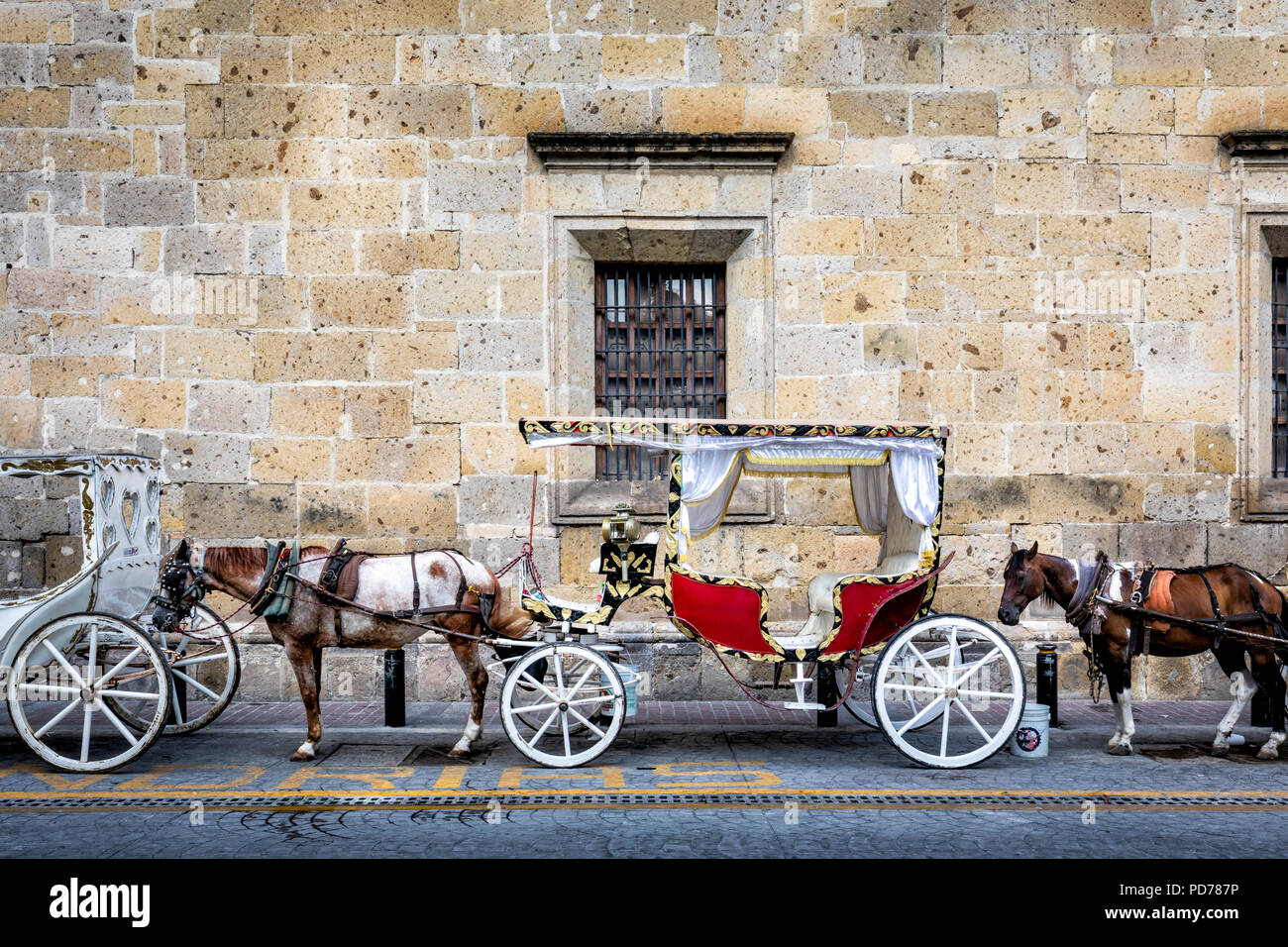 Horse drawn carriages wait for tourists in downtown Guadalajara, Jalisco, Mexico. - Stock Image