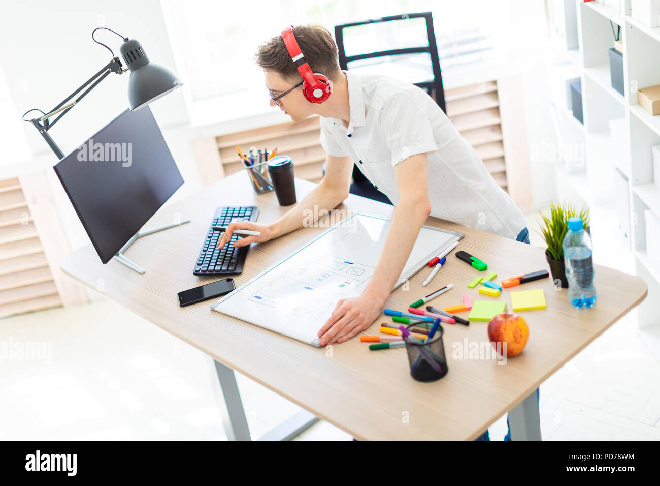 A young man with glasses and headphones stands near a computer desk, holds a marker in his hand and prints on the keyboard. Before him lies a magnetic board and markers. - Stock Image