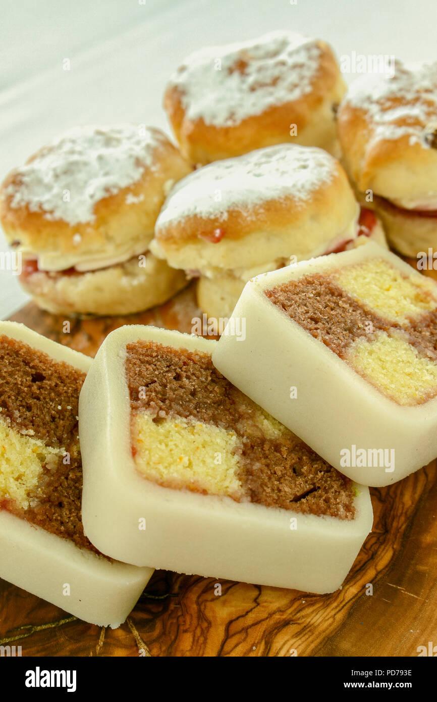 home baked battenberg cake and scones on wooden platter - Stock Image