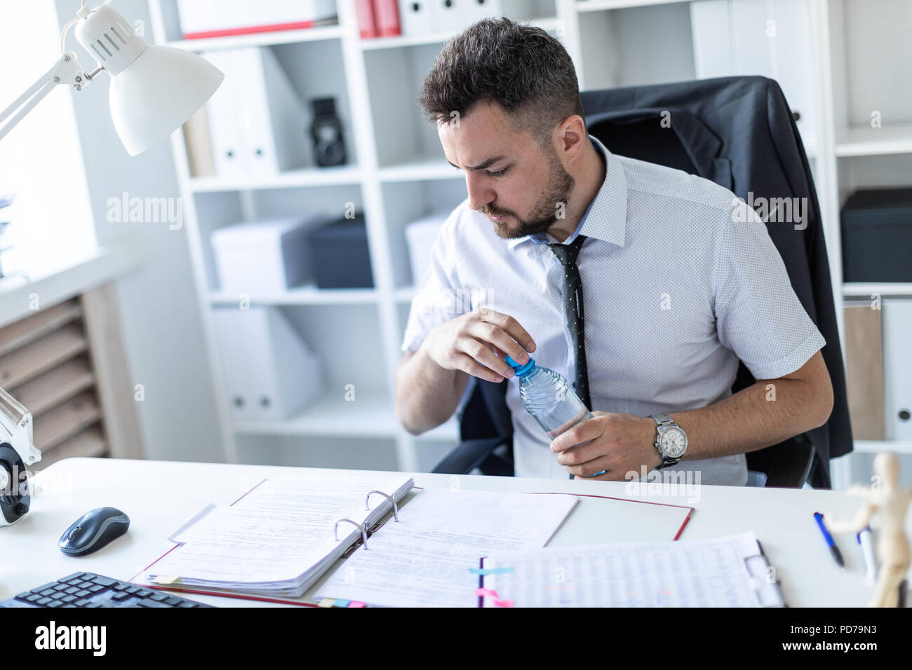 A man is sitting at a table in the office, working with documents and opening a bottle of water. Stock Photo