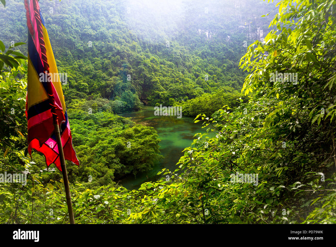 Red flag in the foreground of a high scenic look out point over the lake and other moutnains in the back with mist, rain, fog. - Stock Image