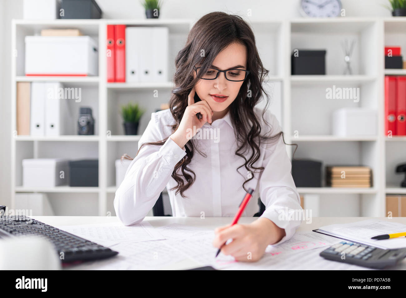 Young girl sits at office desk and fills documents with her left hand. - Stock Image