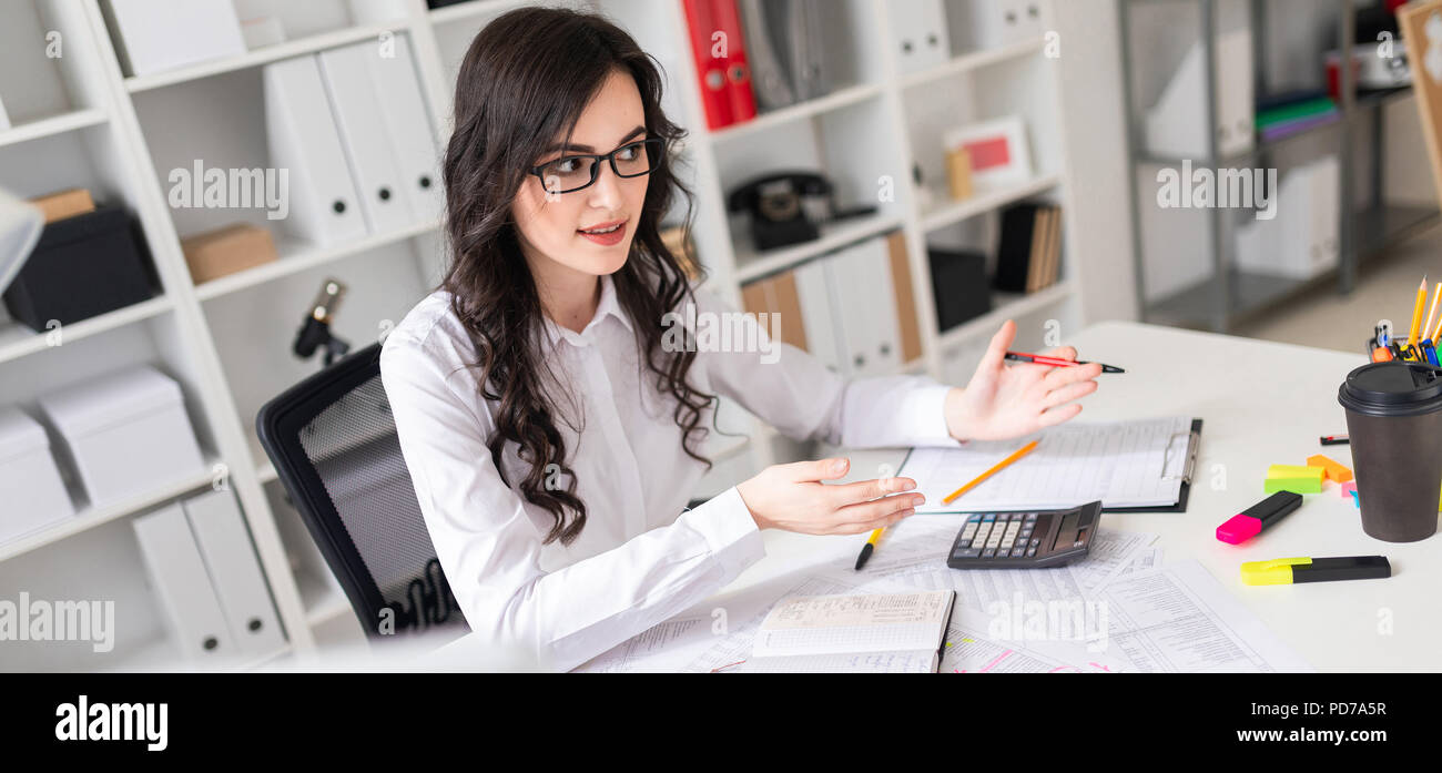 Beautiful young girl is sitting at the table in the office and is holding negotiations. Stock Photo