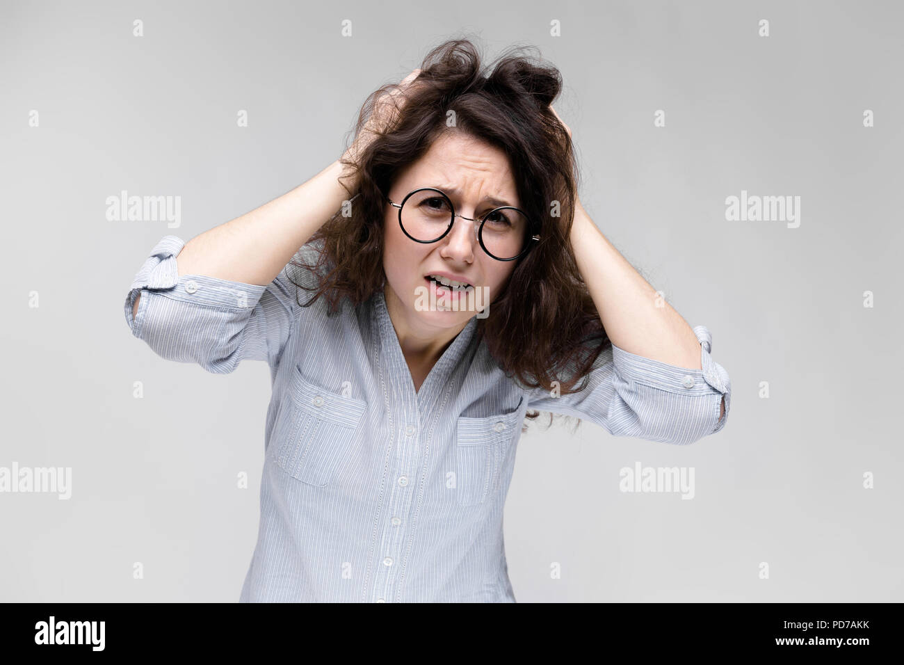 Young brunette girl with glasses. The girl grabbed her head and shouted. - Stock Image