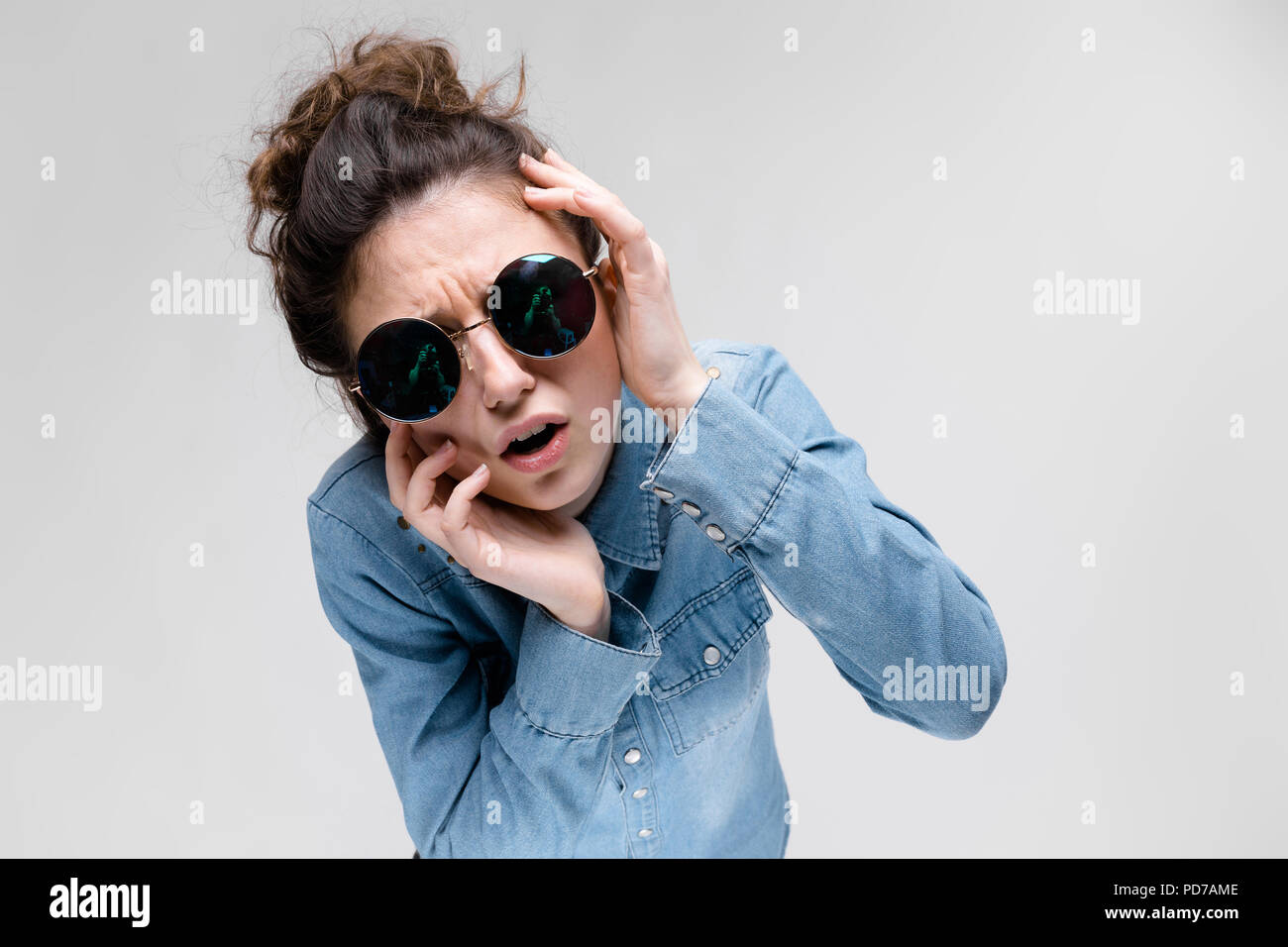Young brunette girl in round glasses. Hairs are gathered in a bun. The girl put her hand to her head. - Stock Image