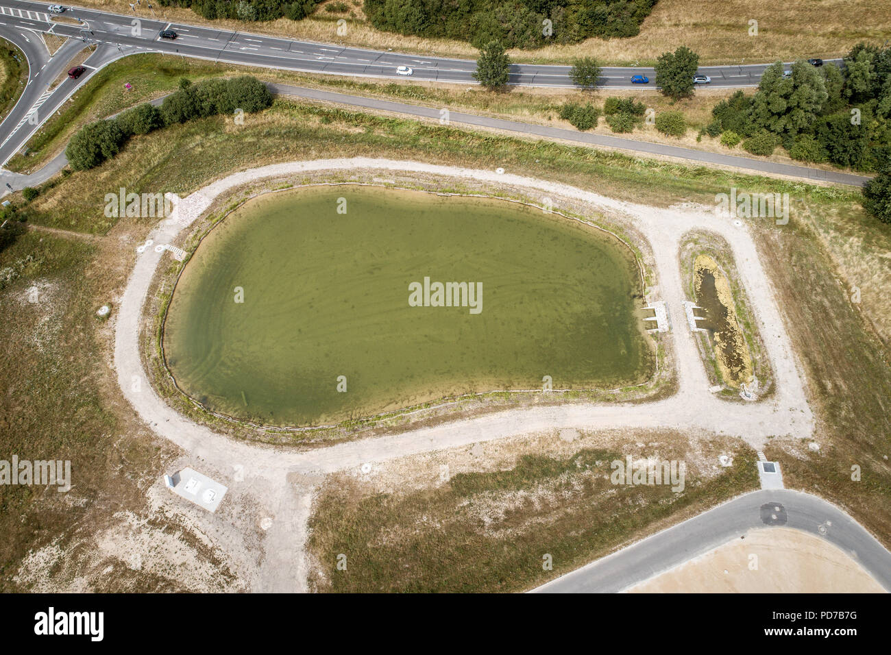 Aerial view of a rain retention basin at the edge of a new development, taken oblique - Stock Image