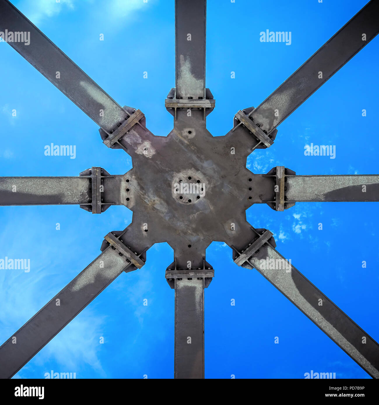Star-shaped supporting structure taken from below against the blue sky, abstract geometric impression. - Stock Image
