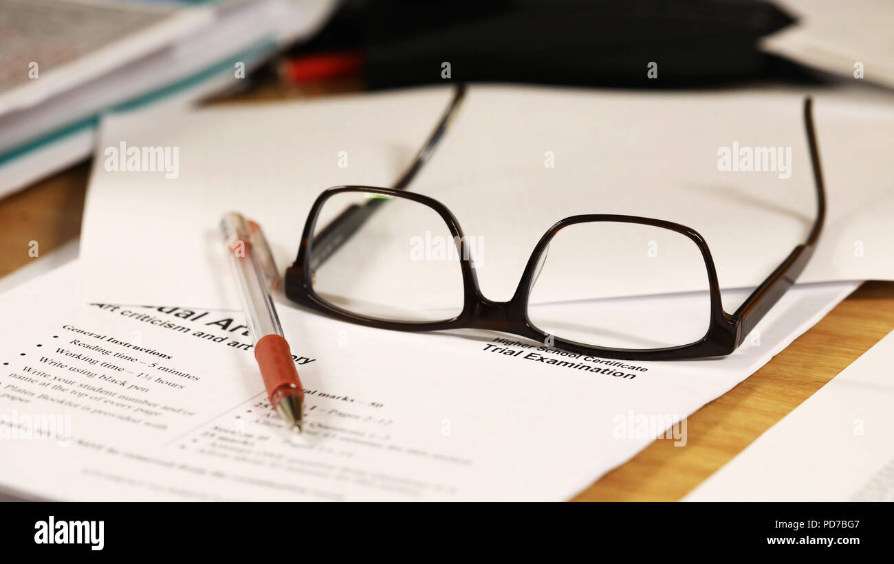 a school teachers desk with glasses and exam paper being marked on it. education, educator, teaching concept. - Stock Image