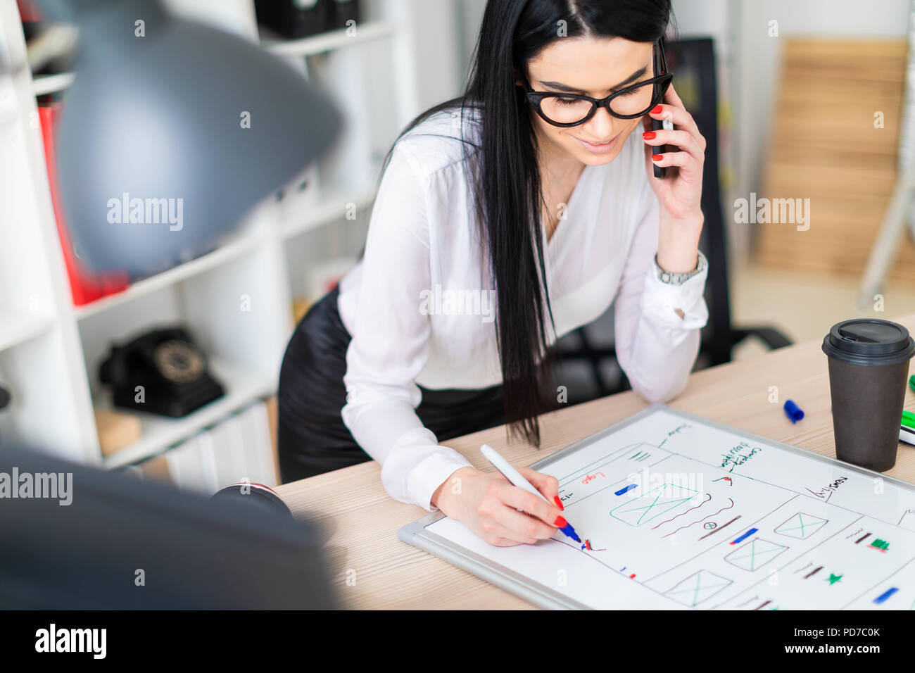 A young girl in glasses stands near a table, talks on the phone and draws a marker on a magnetic board. - Stock Image