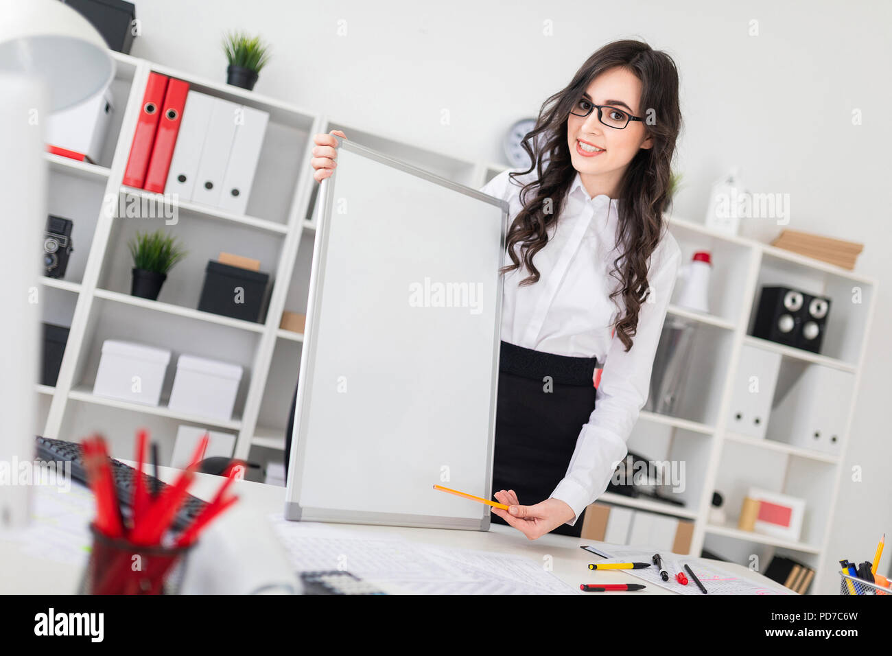Beautiful young girl stands near an office desk and points with a pen on an empty board. - Stock Image