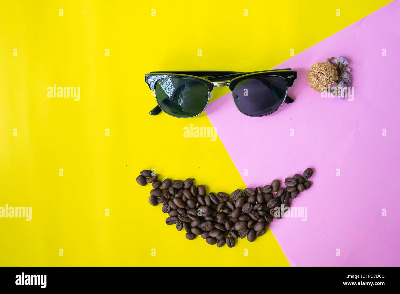 top view flat layer funny face made from coffee beans in smile  icon shape , wooden grinder basket and sun glasses on two tone multicoloured  backgrou - Stock Image