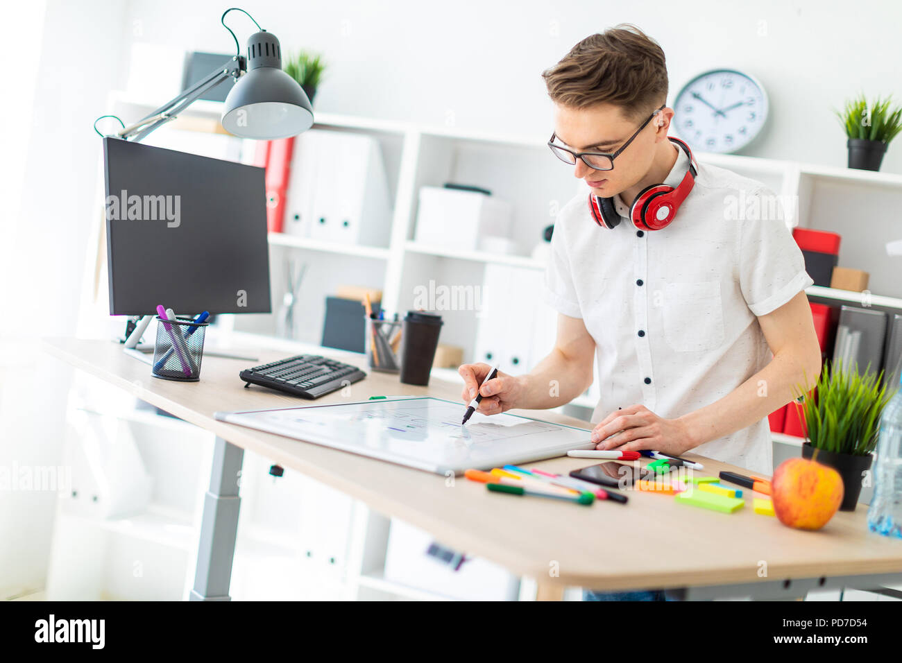 A young man in glasses stands near a computer desk. A young man draws a marker on a magnetic board. On the neck, the guy's headphones hang. - Stock Image