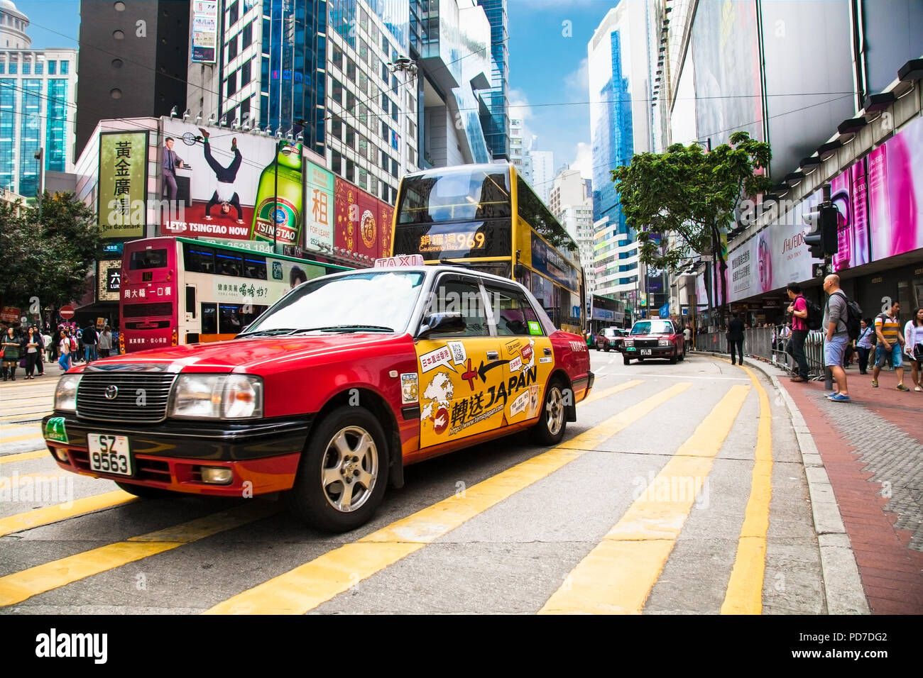 HONG KONG -  APR 3, 2016: Urban red taxi in Hong Kong urban landscape on Apr 3, 2016. Hong Kong is an autonomous territory on the Pearl River Delta of - Stock Image