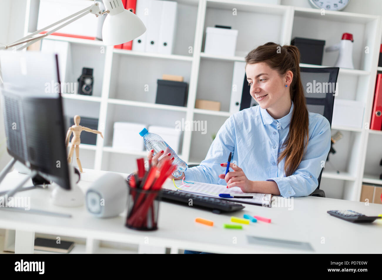 A young girl sits at a table in the office and holds a water bottle and a pen in her hands. - Stock Image