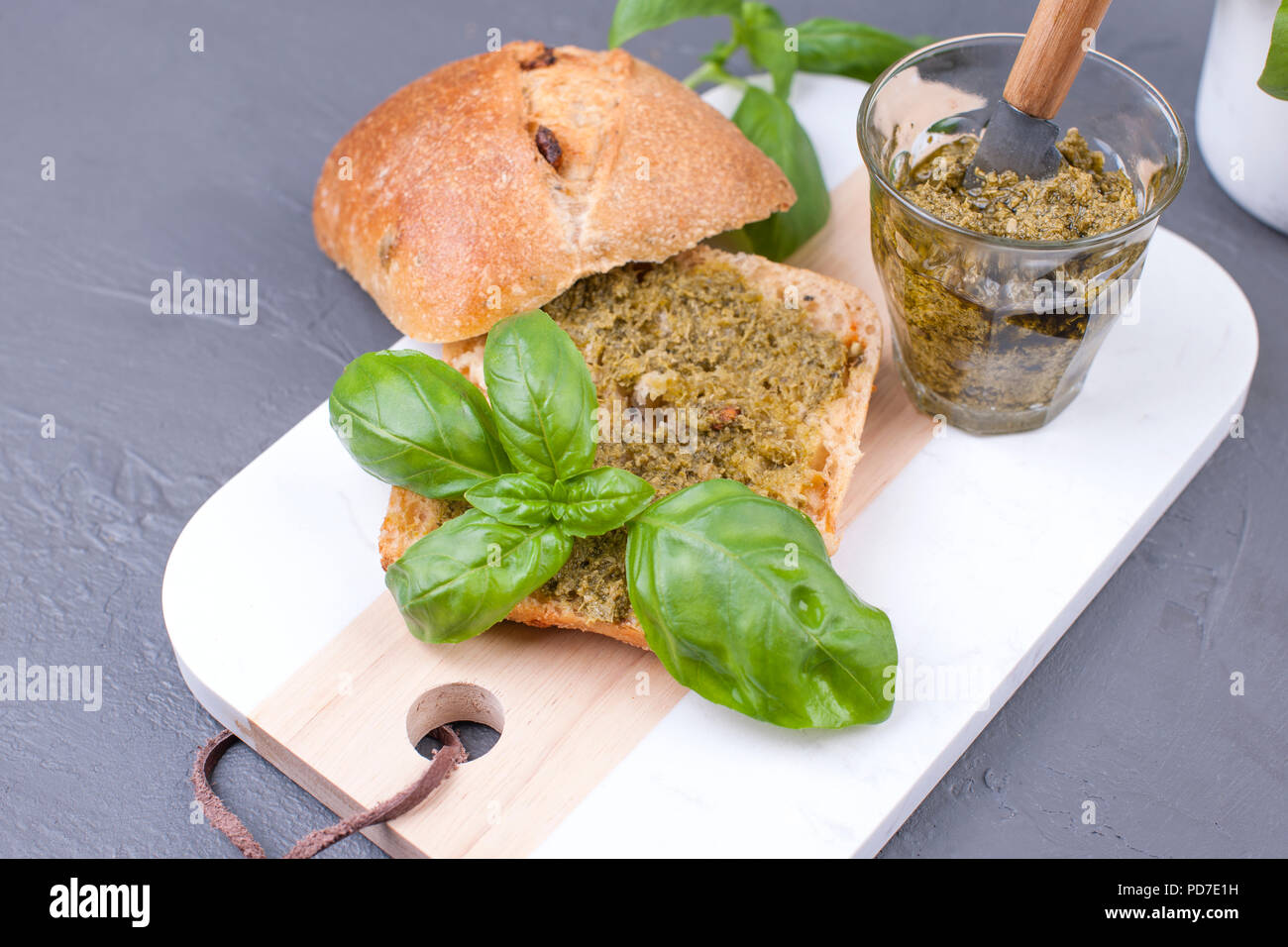 Fresh bread with pesto sauce and green basil on white board. Delicious healthy lunch. Free space for the text. Top view - Stock Image