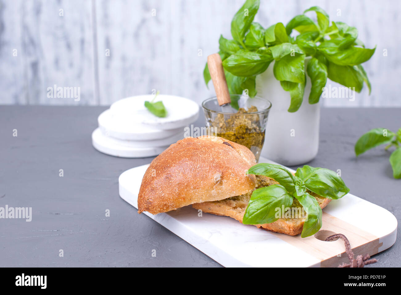 Fresh bread with pesto sauce and green basil on white board. Delicious healthy lunch. Free space for the text. Copy space - Stock Image