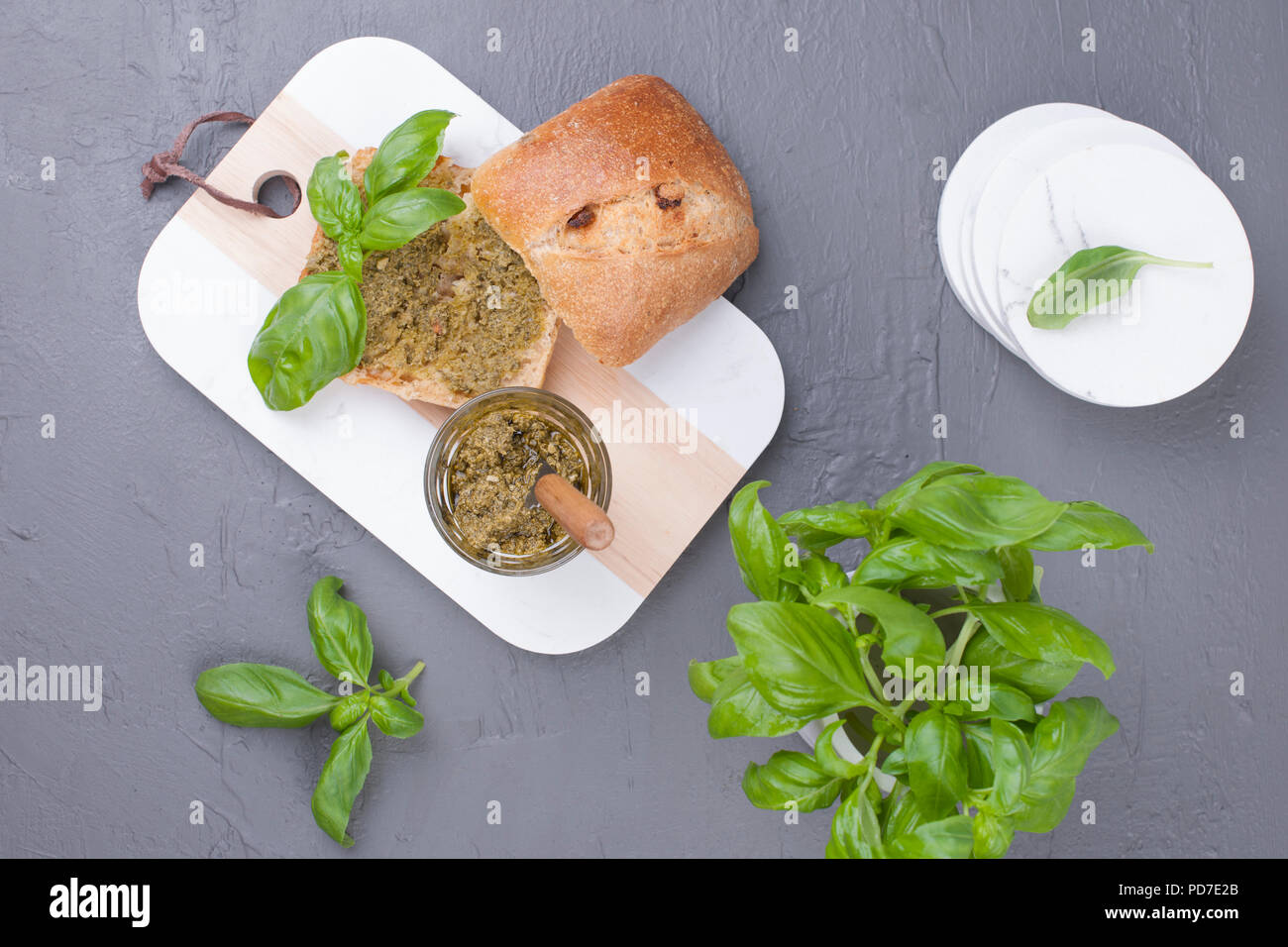 Fresh bread with pesto sauce and green basil on white board. Delicious healthy lunch. Free space for the text. Top view. - Stock Image
