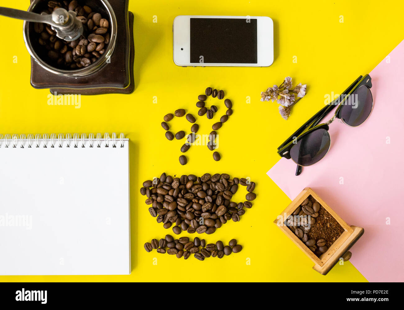 top view flat layer coffee beans in cup and smell icon shape, with vintage wooden coffee grinder, phone,  sun glasses and blank book on two tone multi - Stock Image