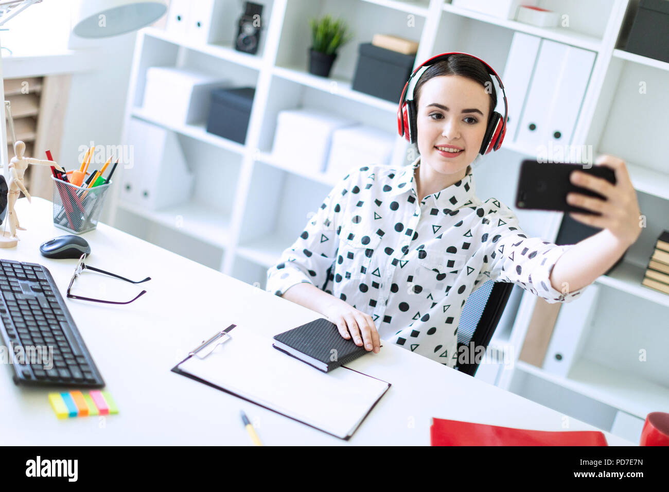 Beautiful young girl sitting in headphones at desk in office and taking pictures of herself on the phone. A photograph with a depth of sharpness, a highlighted focus on the girl. - Stock Image