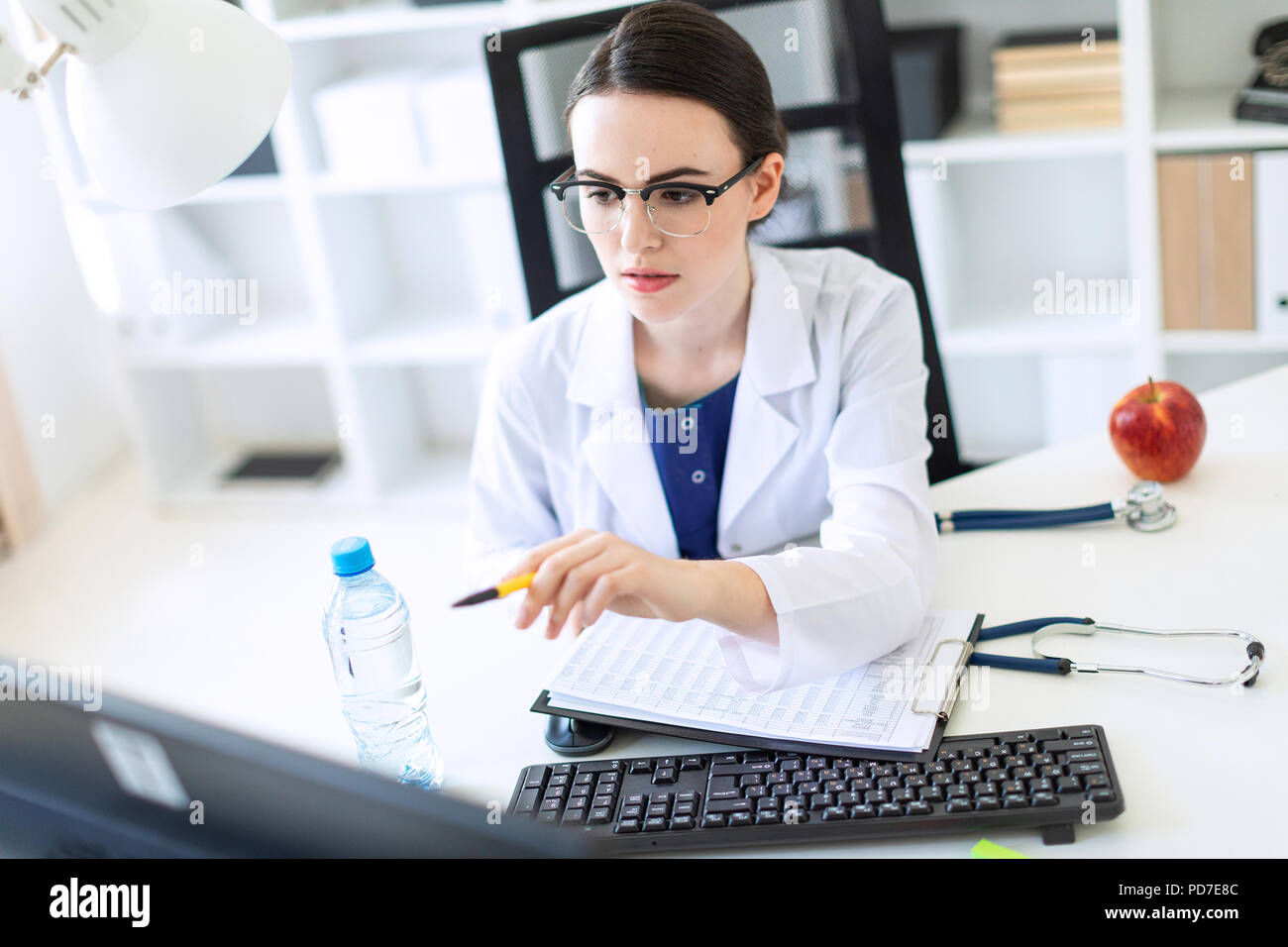 A beautiful young girl in a white robe is sitting at a computer desk with documents and a pen in her hands. - Stock Image