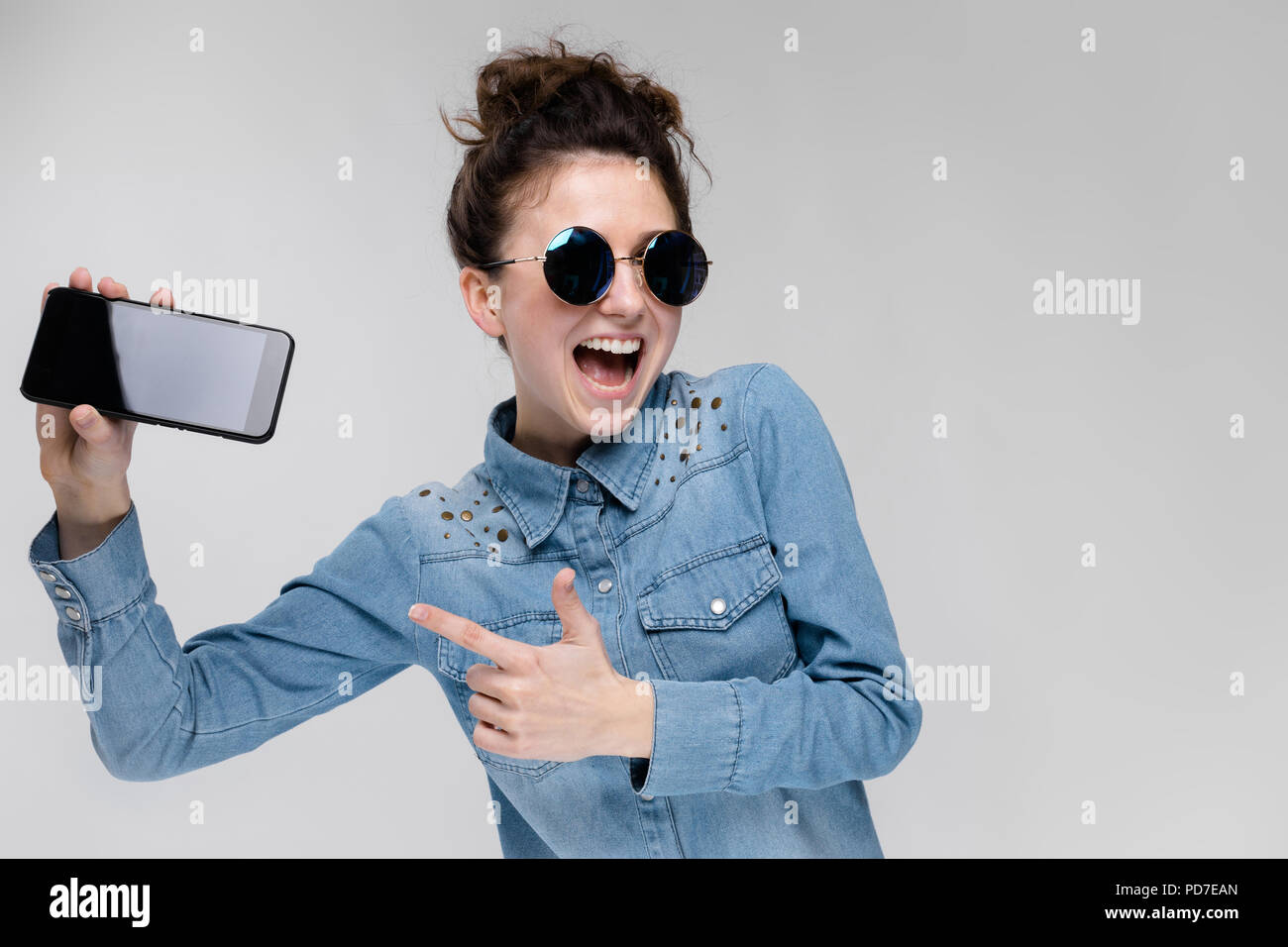 4f3a1c3a3c Young brunette girl in round glasses. Hairs are gathered in a bun. Girl  with a black phone.