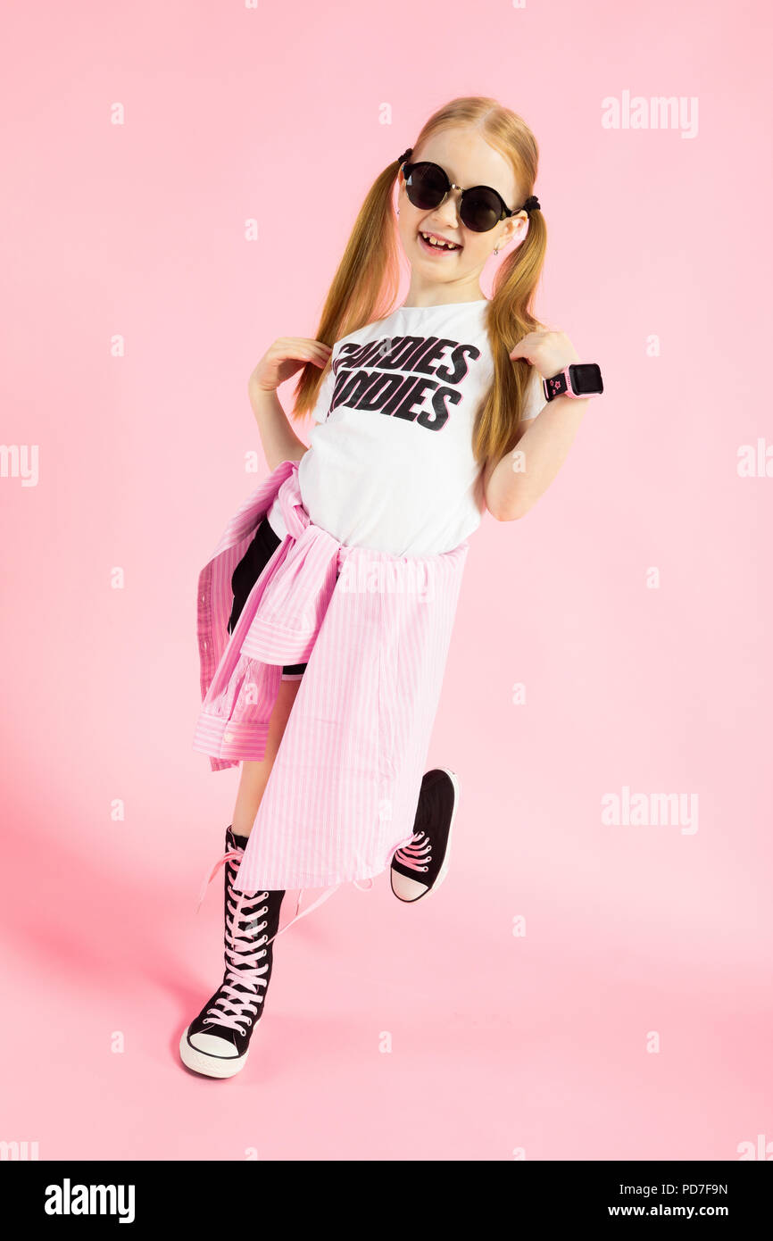 Girl with red tails on a pink background. A charming girl in bright sports clothes and sunglasses bent one leg. - Stock Image
