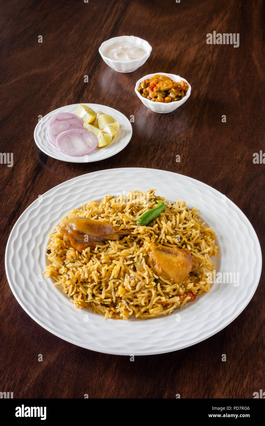 Overhead view from the top of delicious Indian chicken biryani served with traditional sides, salad (raita) and gravy. Natural light used. - Stock Image