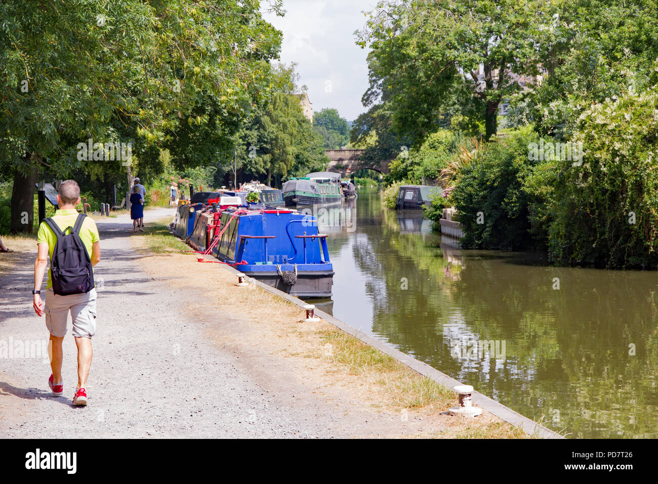 People walk along the Avon and Somerset canal towpath through Bath, England, on a bright sunny day with colourful barges lined up and green overhangin - Stock Image