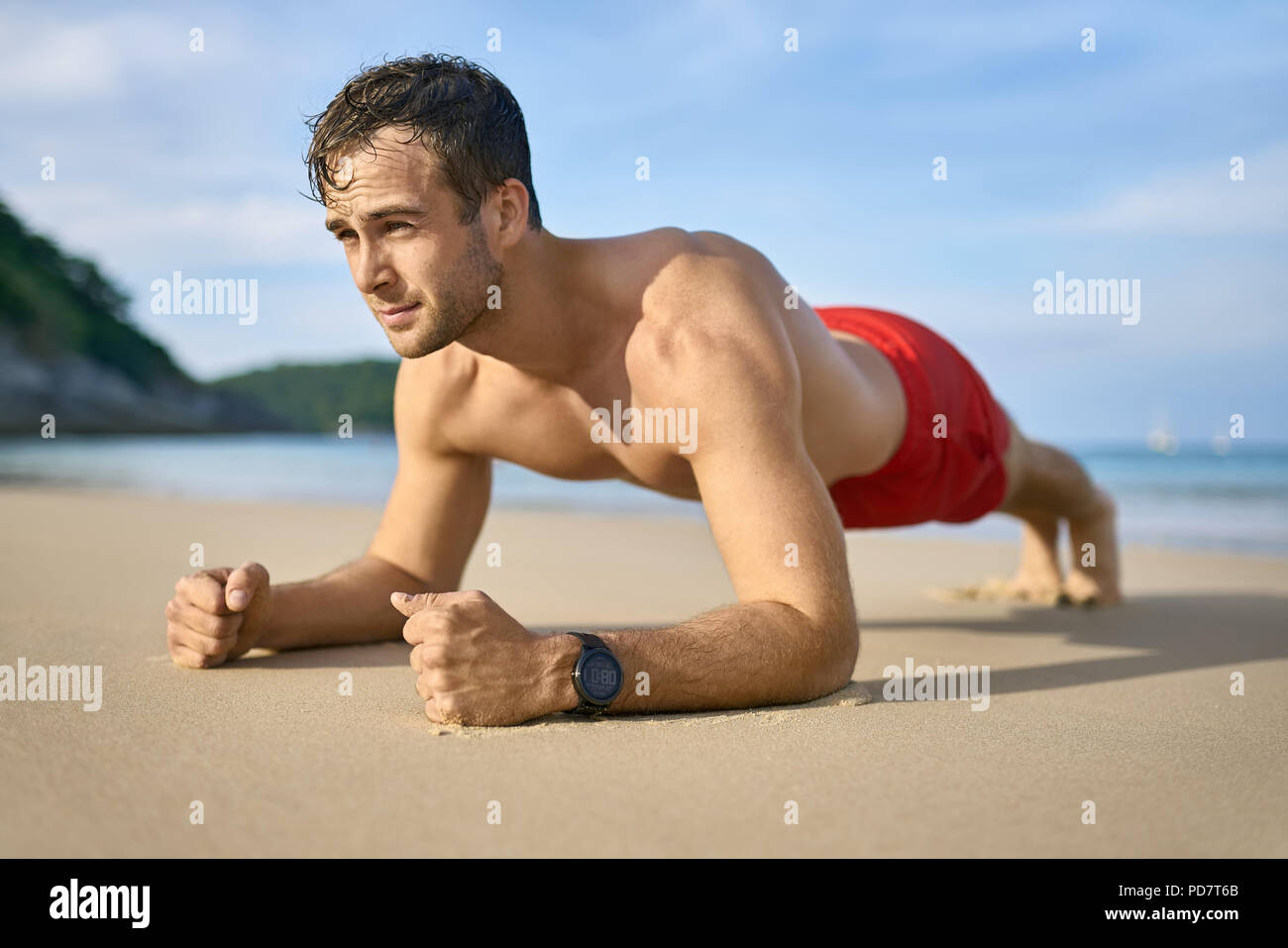 Strong tanned man does a plank on the sand beach on the sunny background of the sea with white boats and the blue sky. He wears a red swim trunks and  - Stock Image