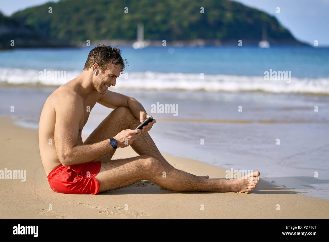 Attractive tanned man sits on the sand beach on the sunny background of the sea with white boats and the green hills. He wears a red swim trunks, whit - Stock Image