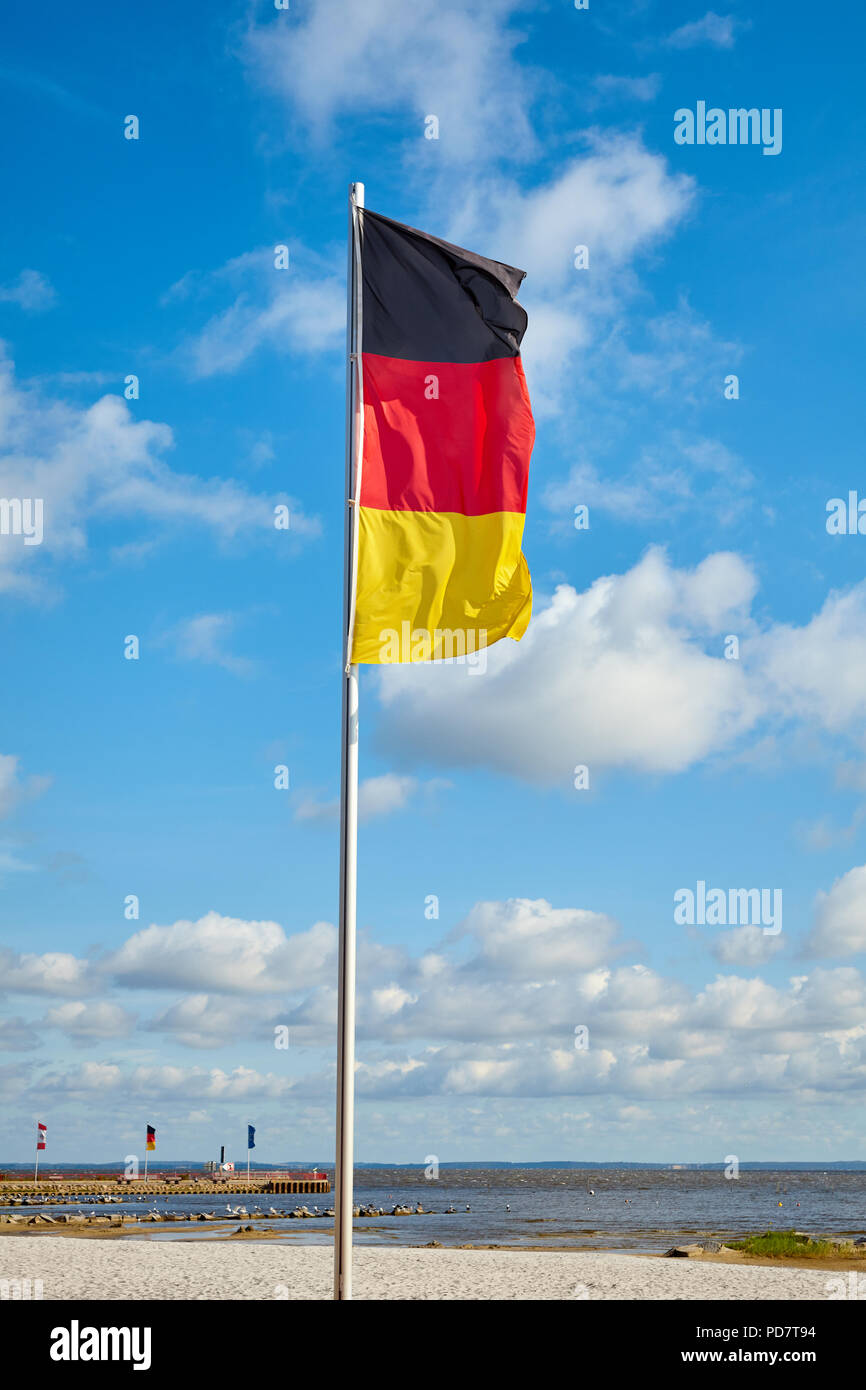 German flag on a pole against the sky on a sunny day. - Stock Image