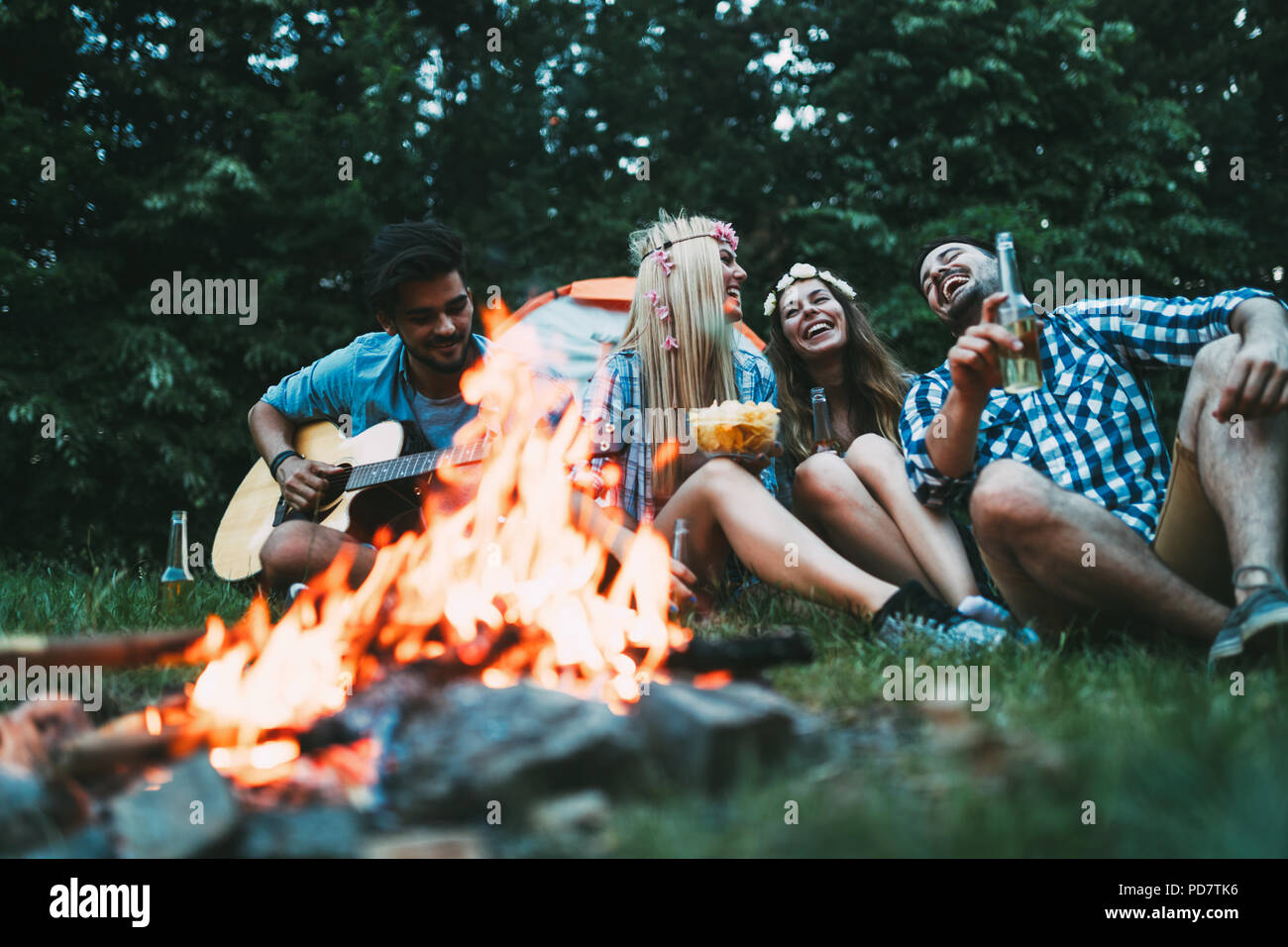 Cheerful young friends having fun by campfire - Stock Image