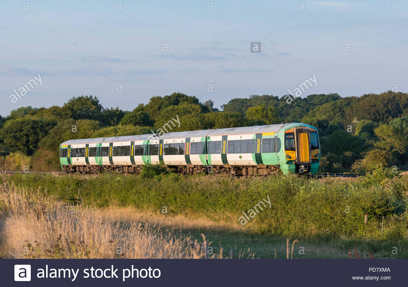 Southern Rail Class 377 Electrostar train travelling through the countryside in the South Downs of the Arun Valley in West Sussex, UK. - Stock Image