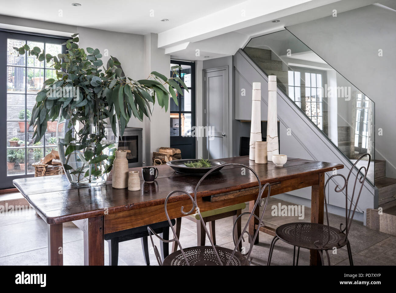 Vintage metal chairs and a pair of Phillipe Hurel stools around wooden table in chic kitchen with wood-burning stove - Stock Image