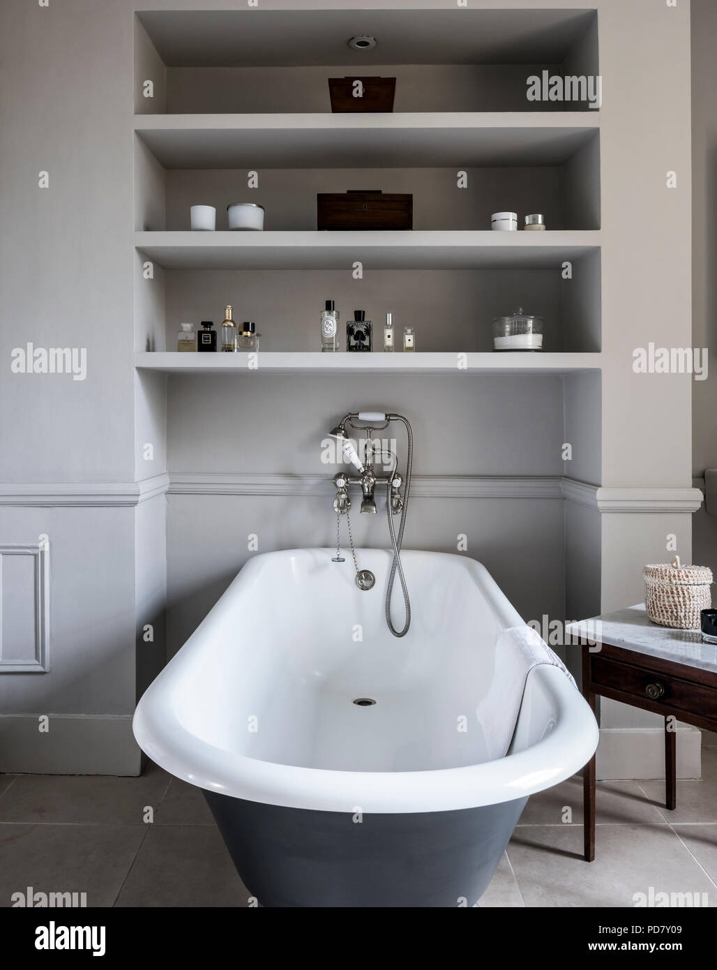 Free-standing roll top bath from Albion in bathroom with antique marble topped table and inbuilt shelving. The outside of the bath is painted in Raili - Stock Image