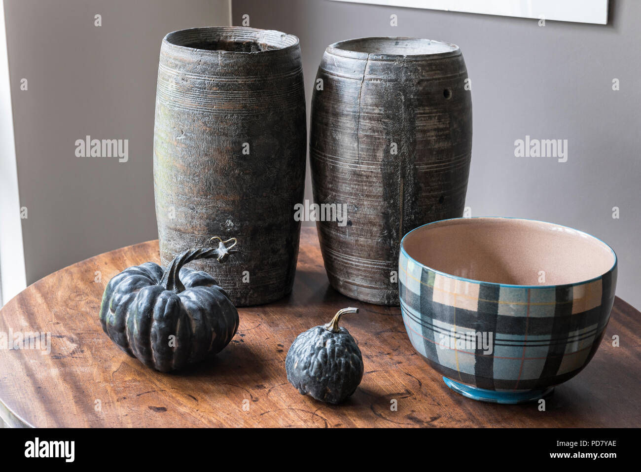 Two wooden pots from South Africa are displayed on a small table in the living room with dried gourds and a bowl from Anta. Stock Photo