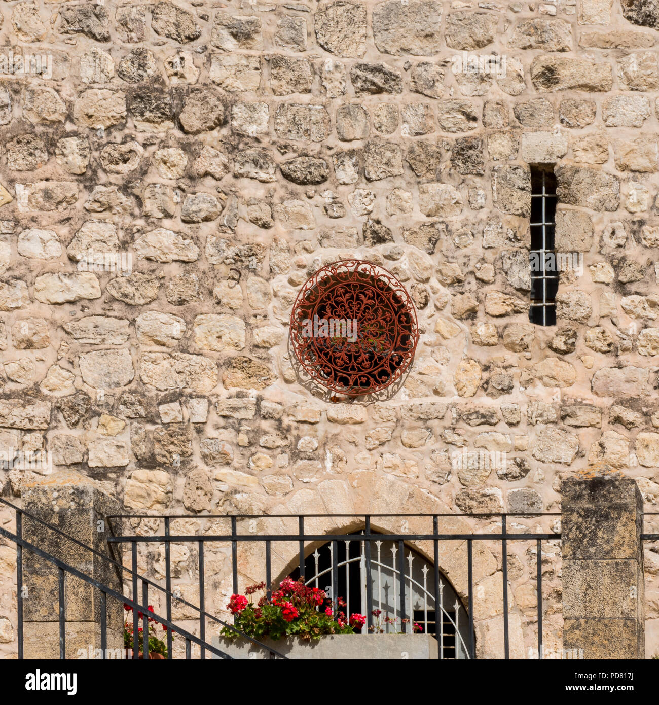 Ornate Round Red Metalwork Window In The Stone Wall Of John The