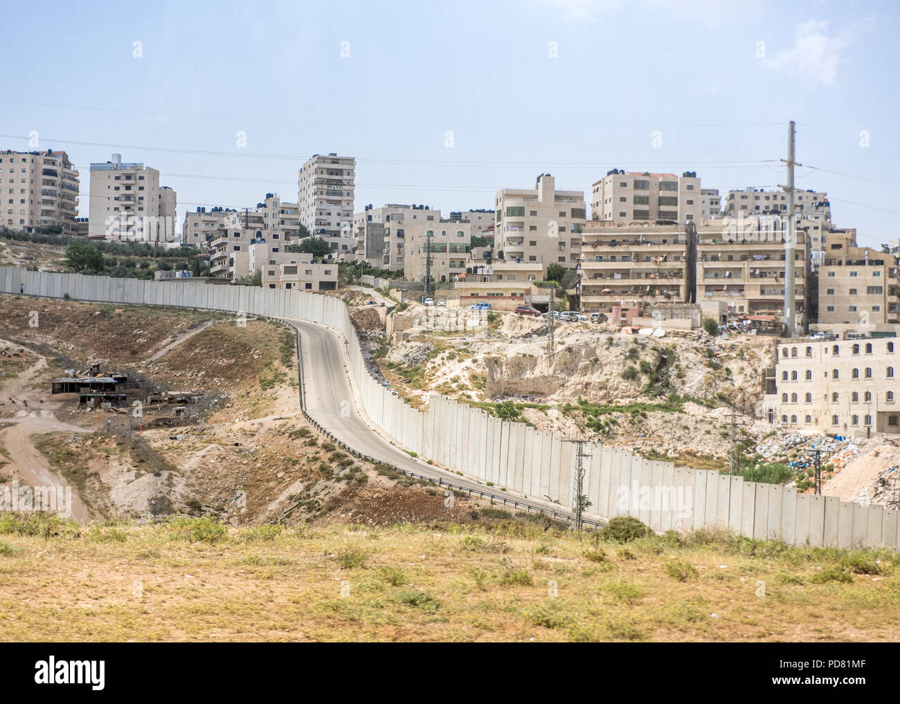 View from the Dead Sea to Jerusalem road in the West Bank Palestinian area of the Separation Barrier, here a high concrete wall, and Israeli apartment - Stock Image