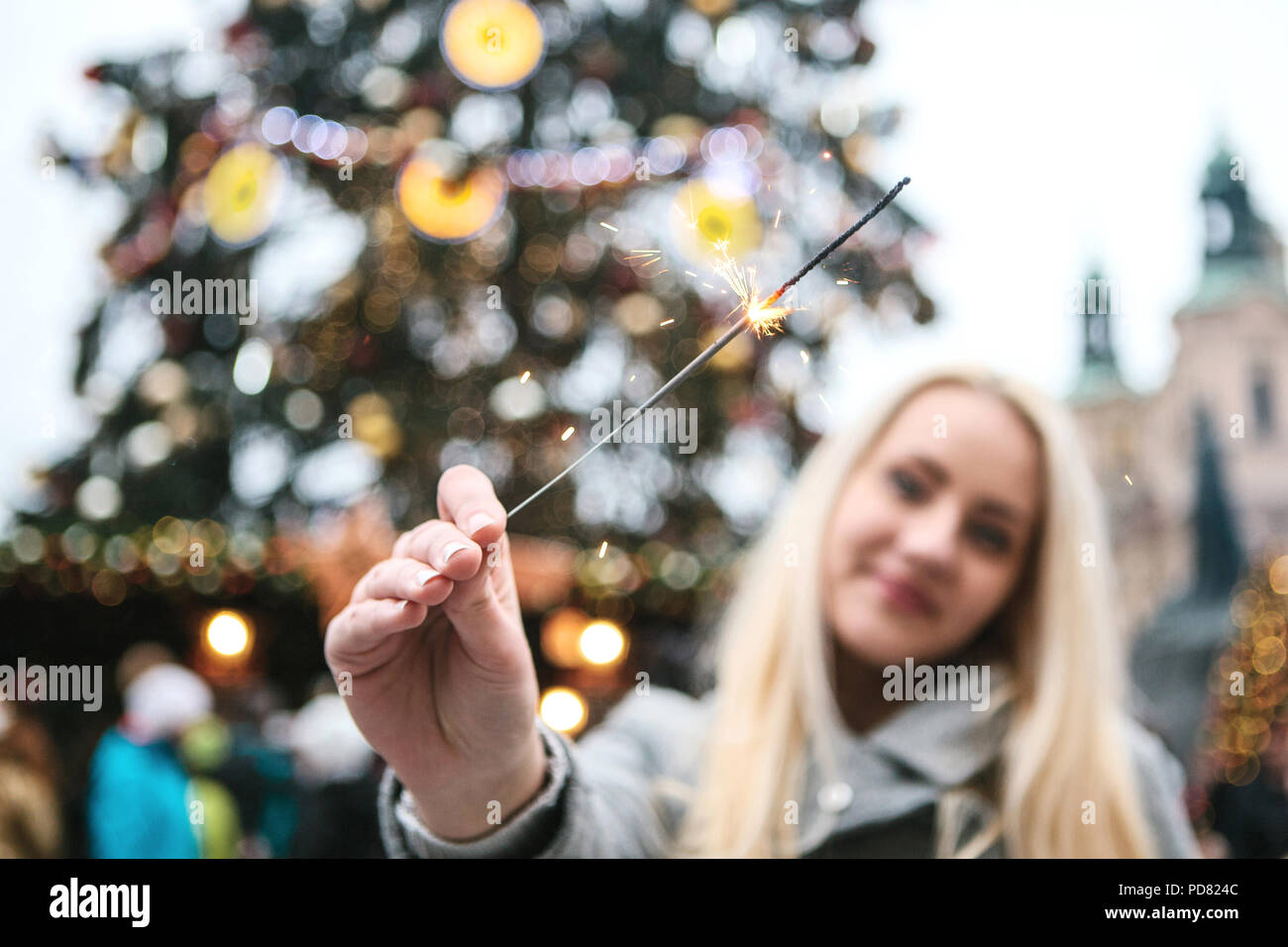 The girl is holding a Bengal fire in her hand during the celebration of Christmas. Old Town Square and Christmas Tree in Prague in the Czech Republic in the background. - Stock Image
