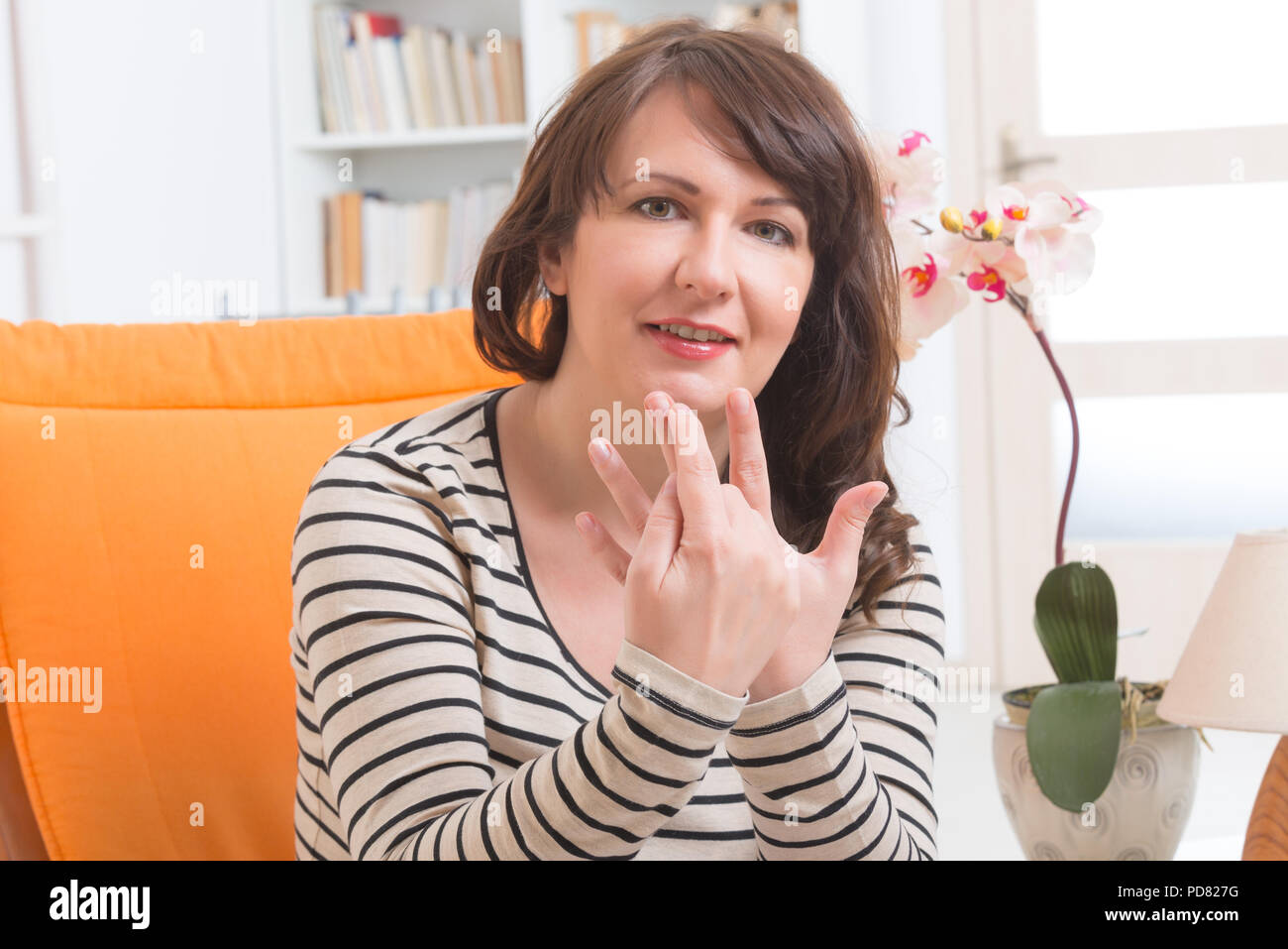 Woman doing EFT on the finger point. Emotional Freedom Techniques, tapping, a form of counseling intervention that draws on various theories of altern - Stock Image