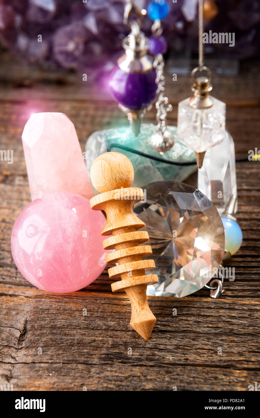 Pendulums.Wooden, crystal pendulum, amethyst, tool for dowsing. Crystals undrneath and in backbround. - Stock Image