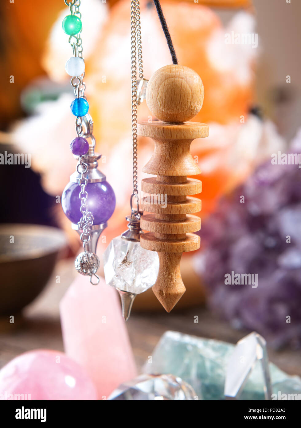 Pendulums crystal pendulum, amethyst, tool for dowsing. Crystals undrneath an in backbround. - Stock Image