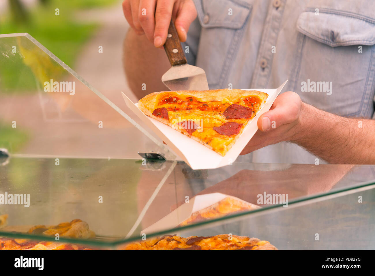 A street food vendor selling pizza by slice outdoors - Stock Image