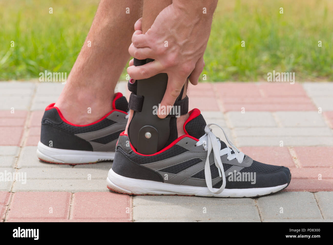 Man in athletic sneakers wearing ankle orthosis or brace - Stock Image